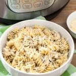 Cooked pasta and chicken in a bowl sitting beside Instant Pot.