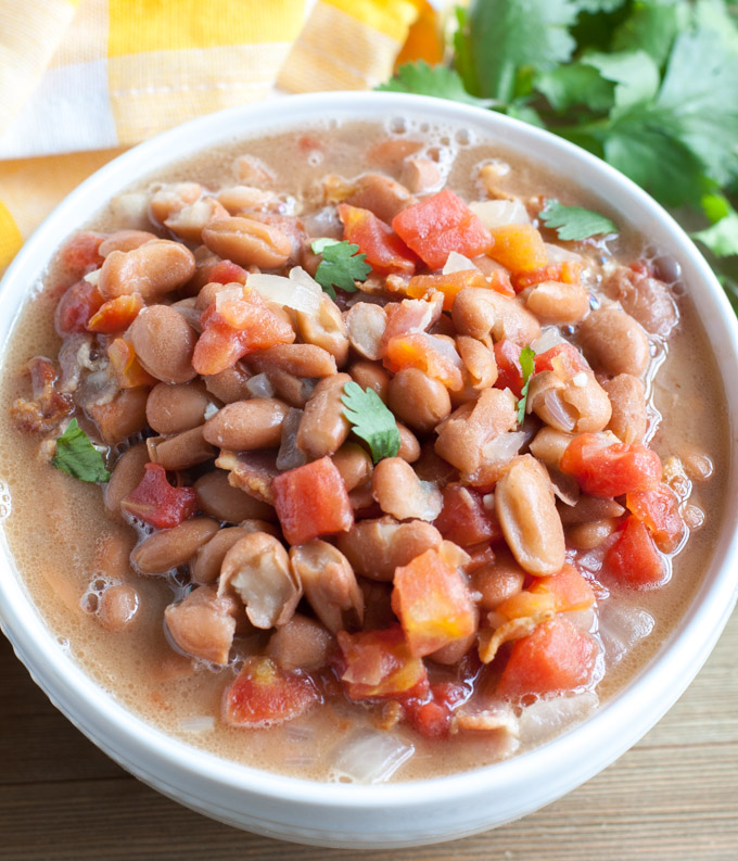 A large bowl of charro beans with cilantro on the side