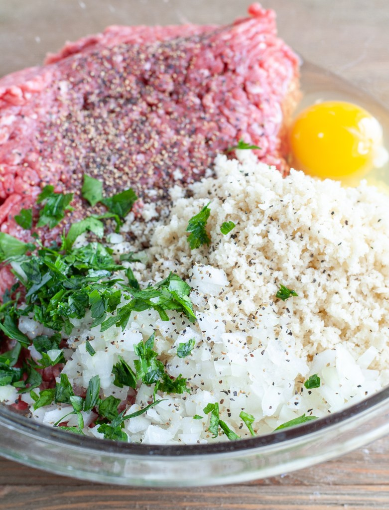 Ground beef, parsley, onion, panko, egg in a glass bowl