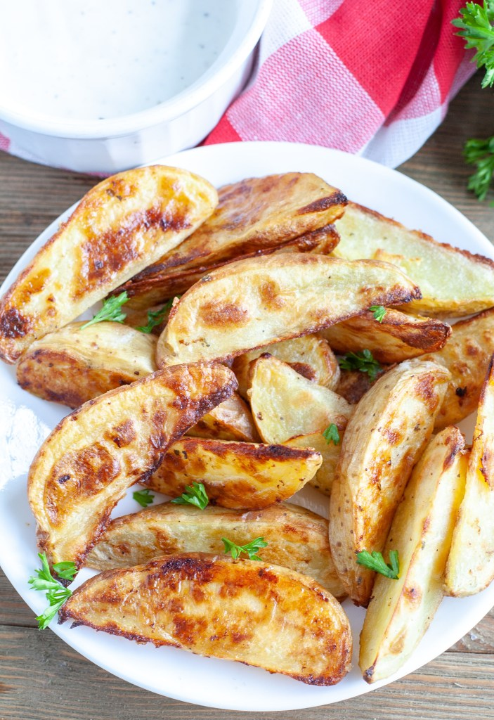 Potato wedges on a plate with ranch dipping sauce
