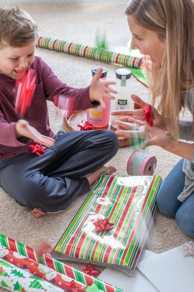 A women and little boy with wrapped present.