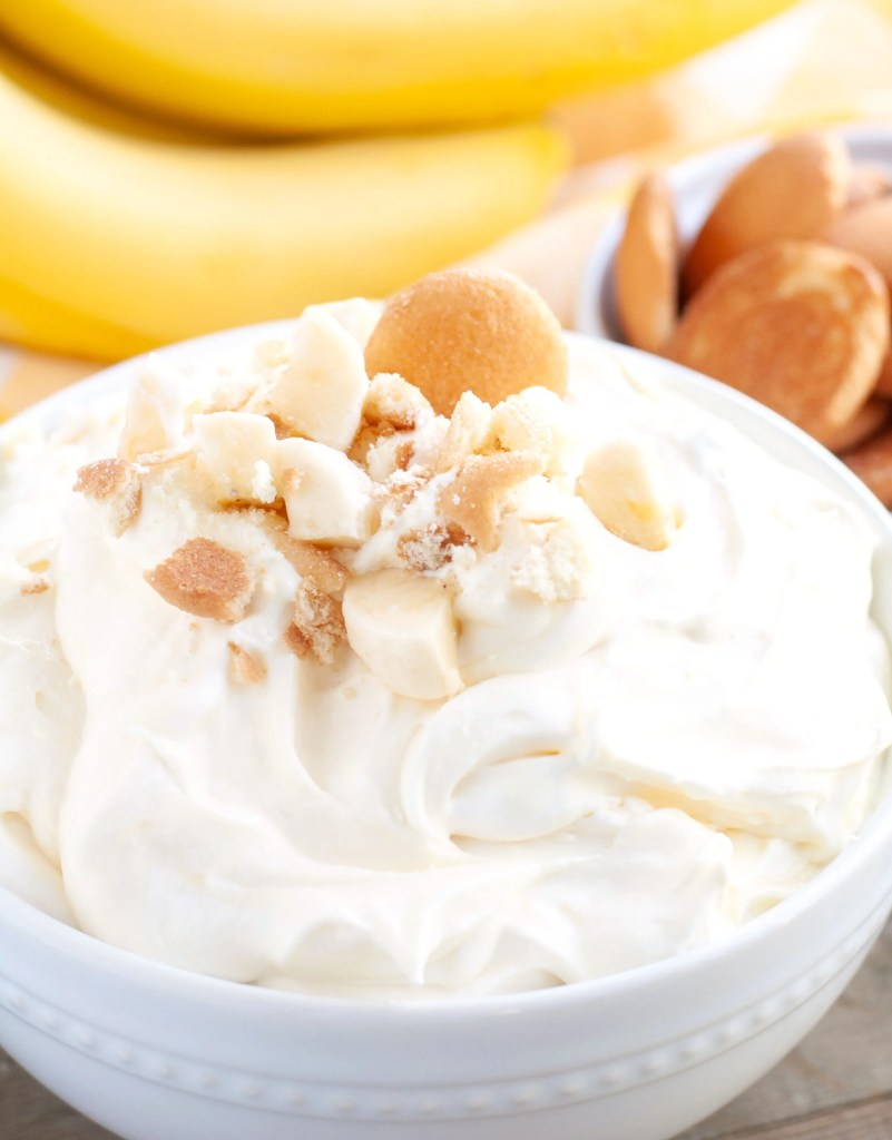 Banana Pudding Dip in a bowl with crushed cookies and diced bananas