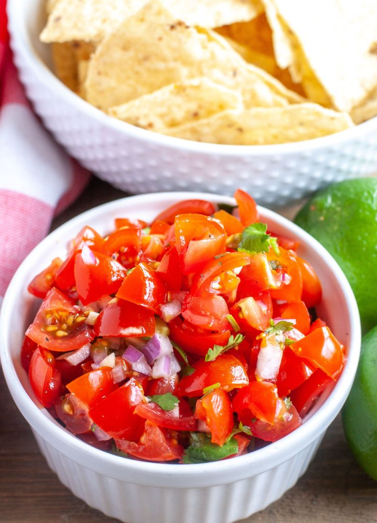 Small bowl of pico de gallo with a bowl of tortilla chips