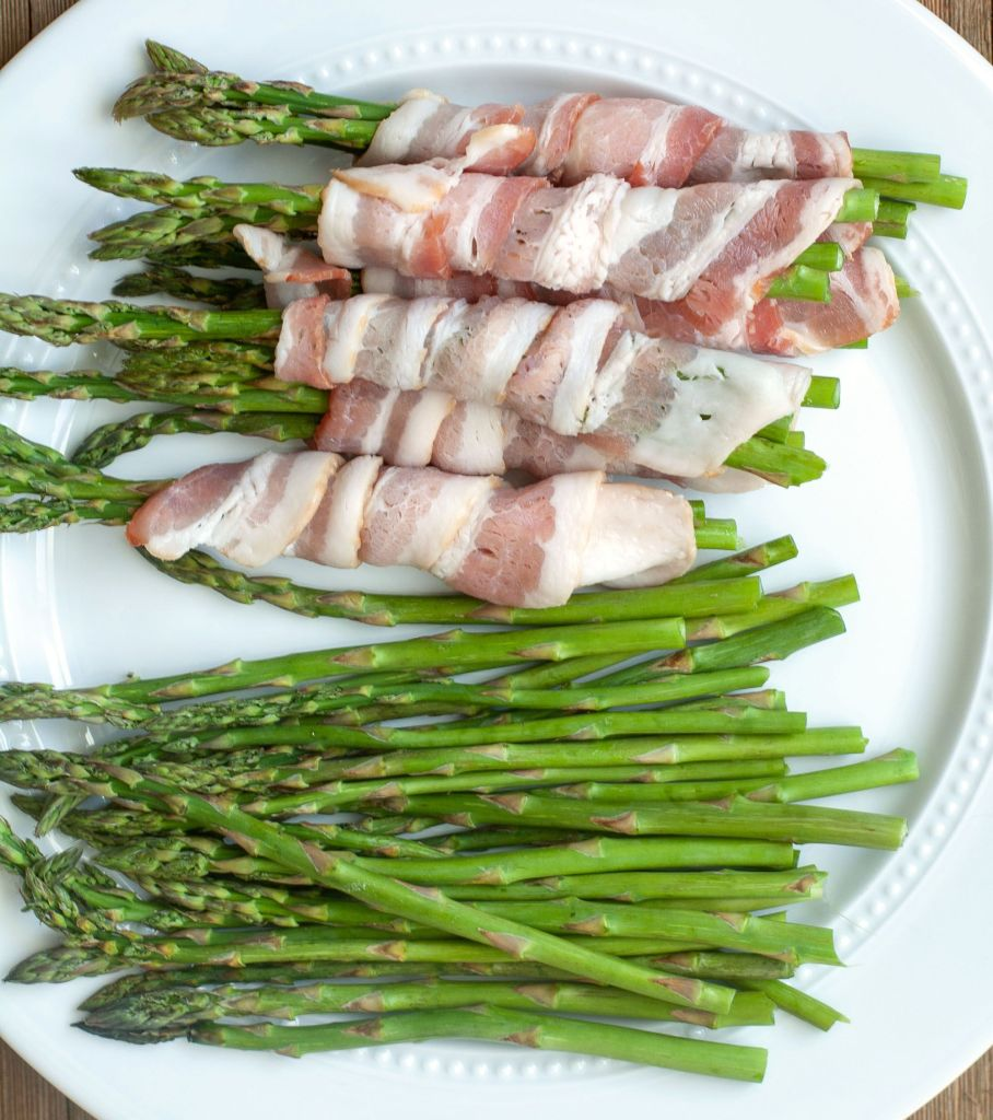 Bacon wrapped around asparagus on a plate