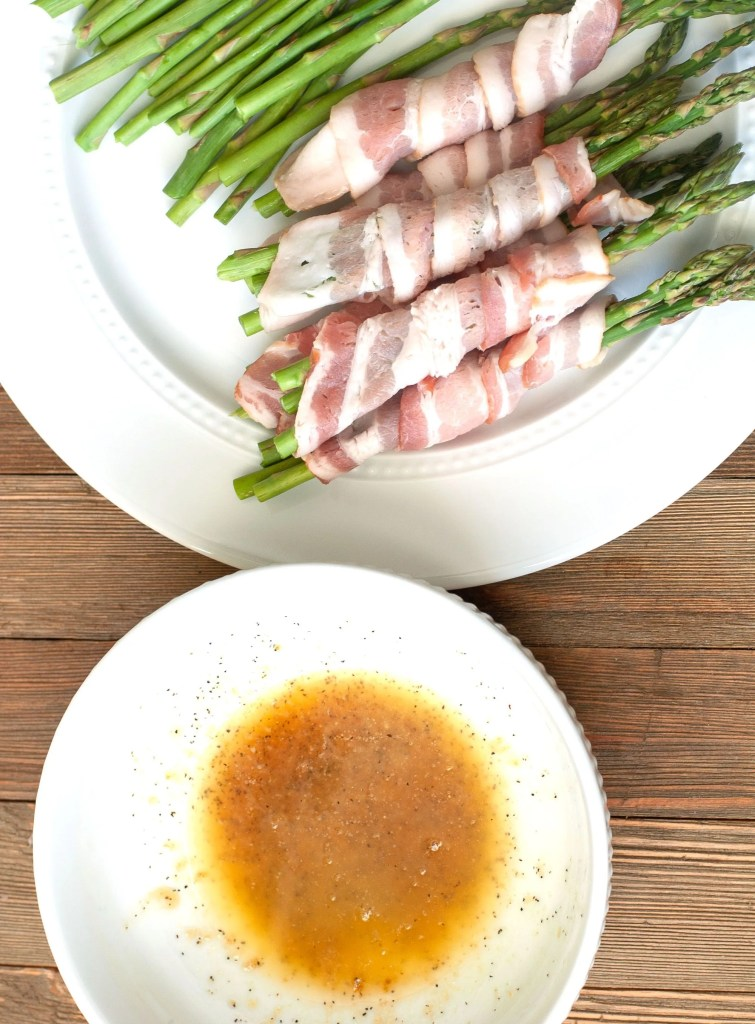 Melted butter and brown sugar in a bowl with bacon wrapped around asparagus