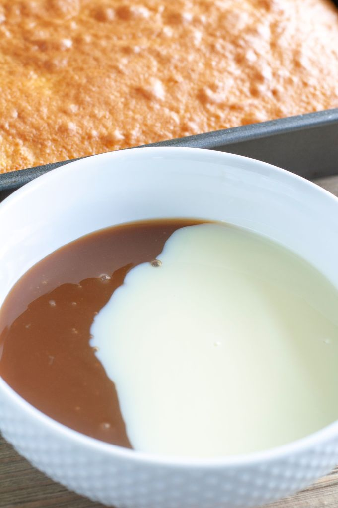 A bowl with sweetened condensed milk and caramel sauce and cake in the background