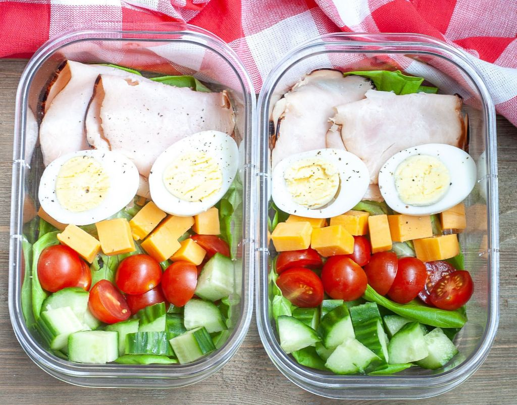 2 containers with turkey, hard boiled eggs, cheese, tomatoes and cucumber.