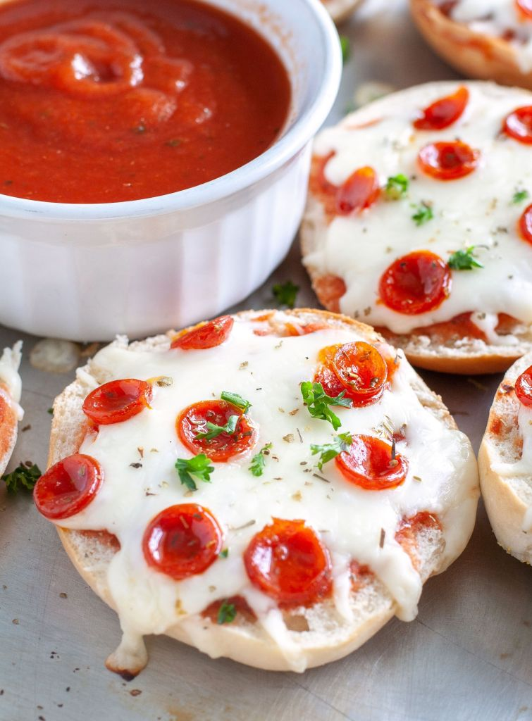 Pizza Bagels on a pan and bowl of marinara sauce