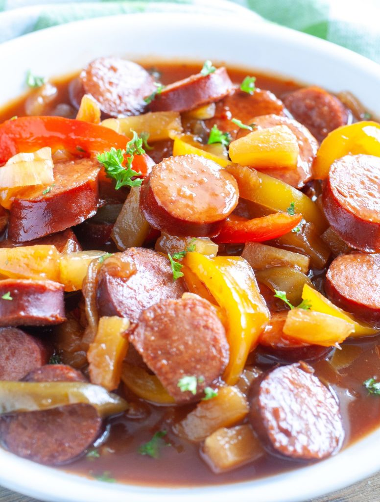 A bowl of sweet and sour kielbasa with onions and peppers