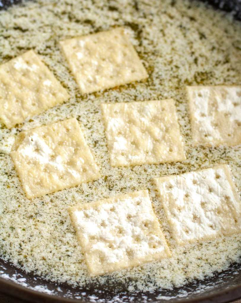 Crackers laying in melted butter and seasoning.