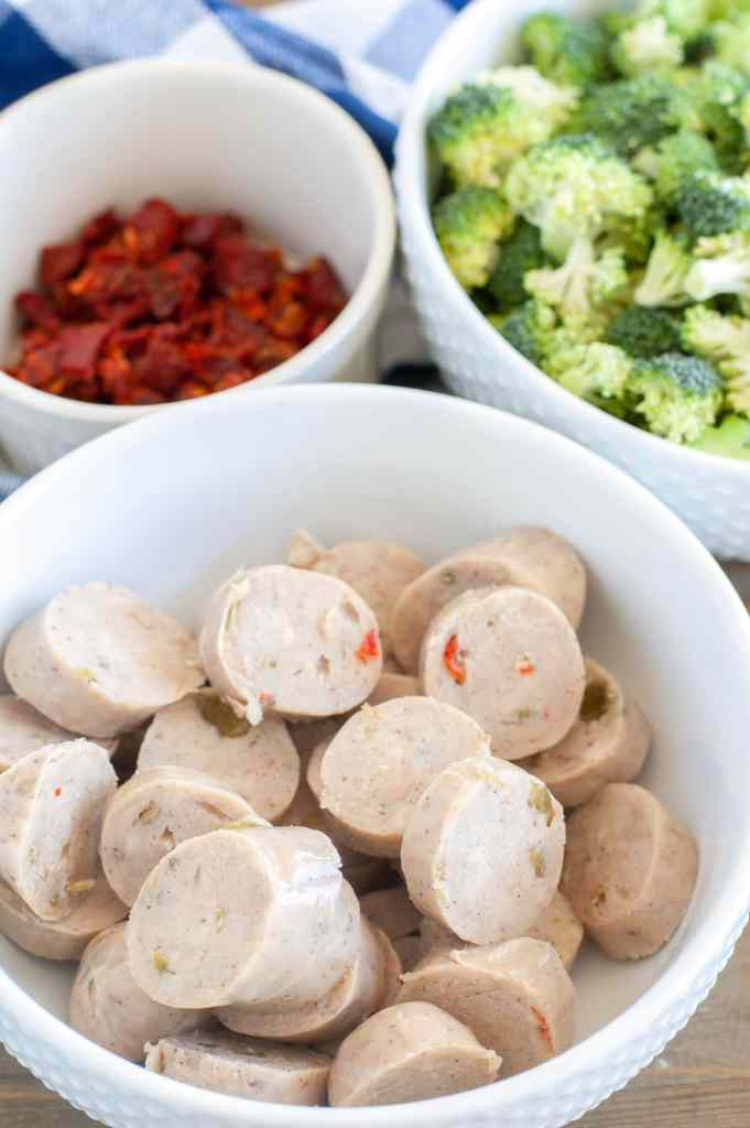 a bowl of chicken sausage. a bowl of sun dried tomatoes and a bowl of broccoli