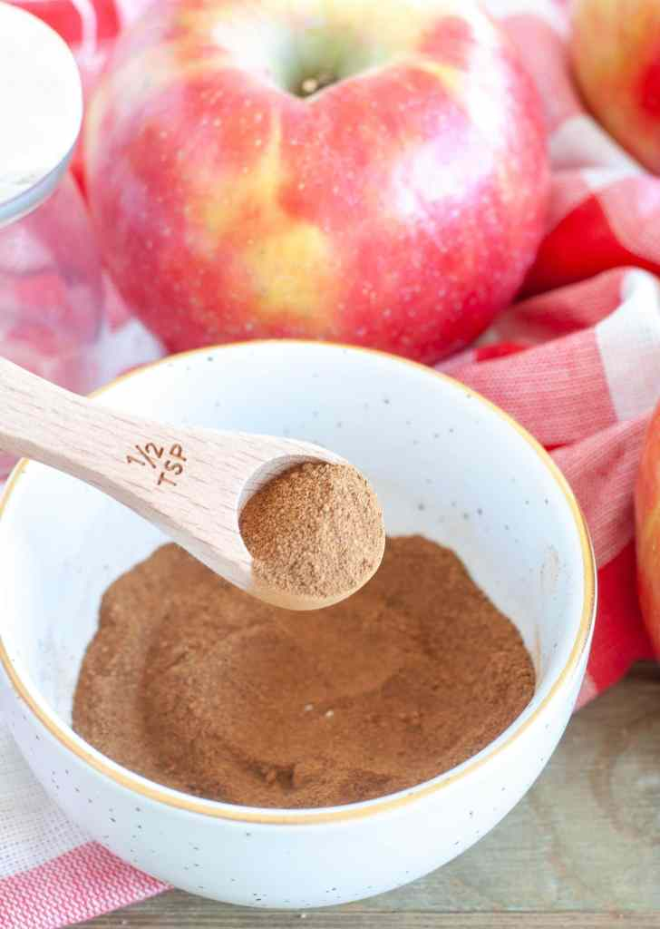 Apple pie spice in a white bowl with a teaspoon