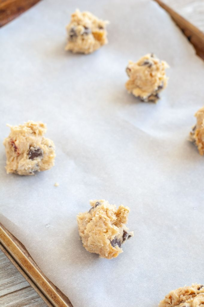 Scoops of chocolate chip cookies on a baking sheet
