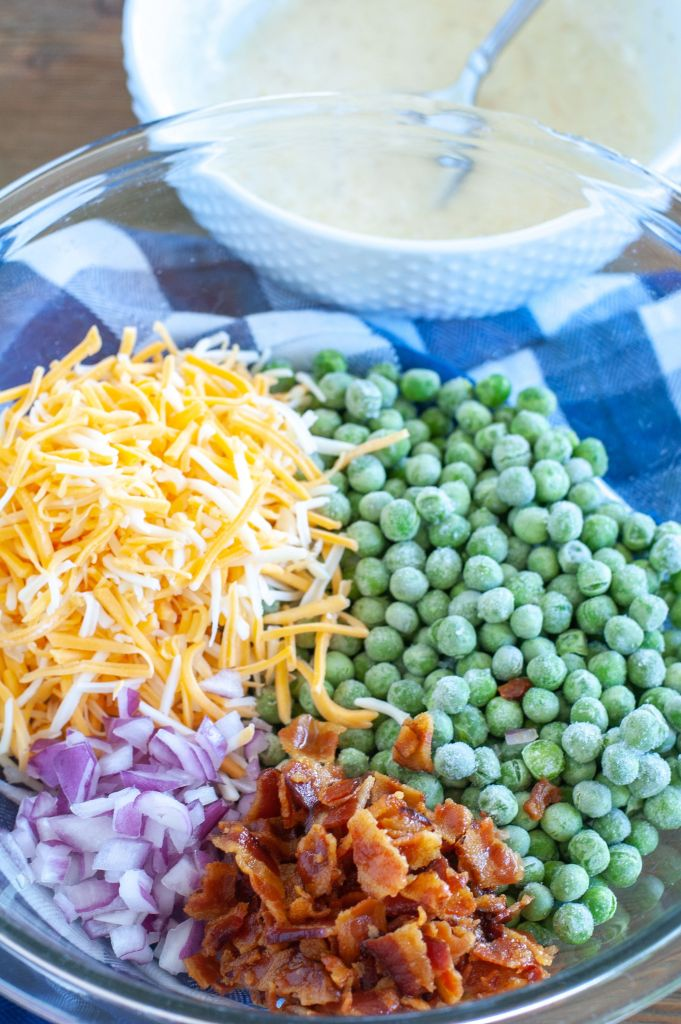 Cheese, red onion, bacon, peas in a bowl with dressing in a separate bowl