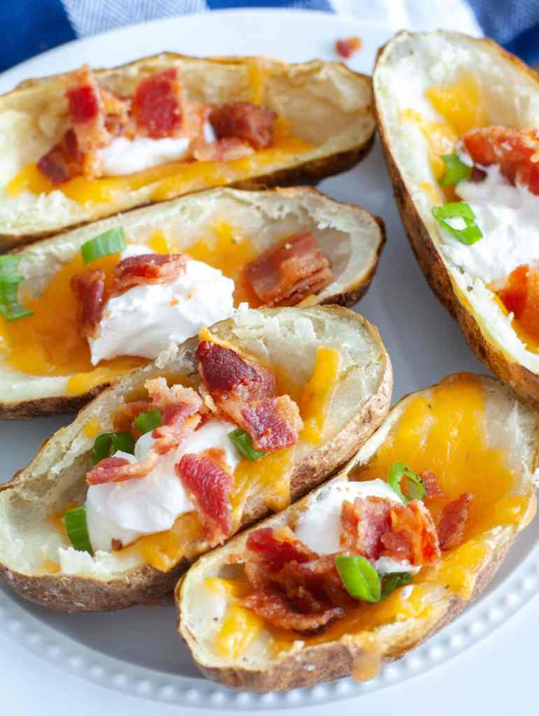 Plate of air fryer potato skins loaded with sour cream, cheese and bacon.