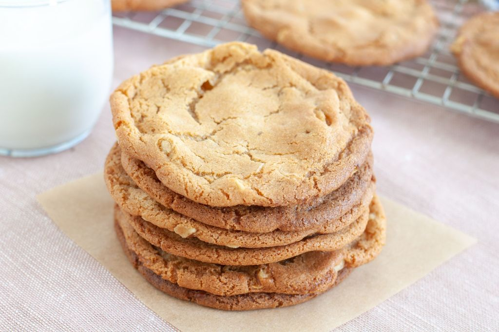 Stack of butterscotch cookies with a glass of milk in background