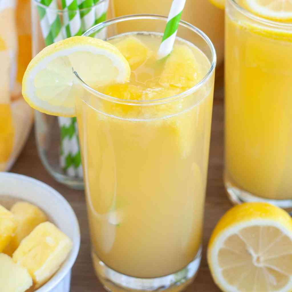 Pineapple lemonade in a glass with green striped straw