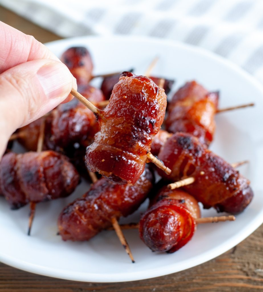 hand holding bacon wrapped smokie