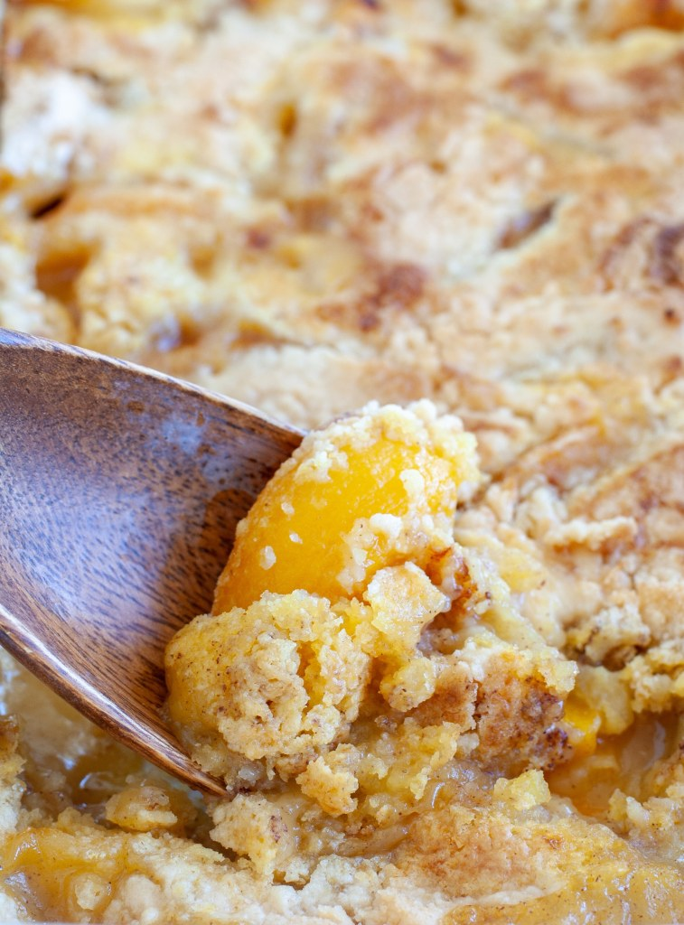 Wooden spoon in peach cobbler