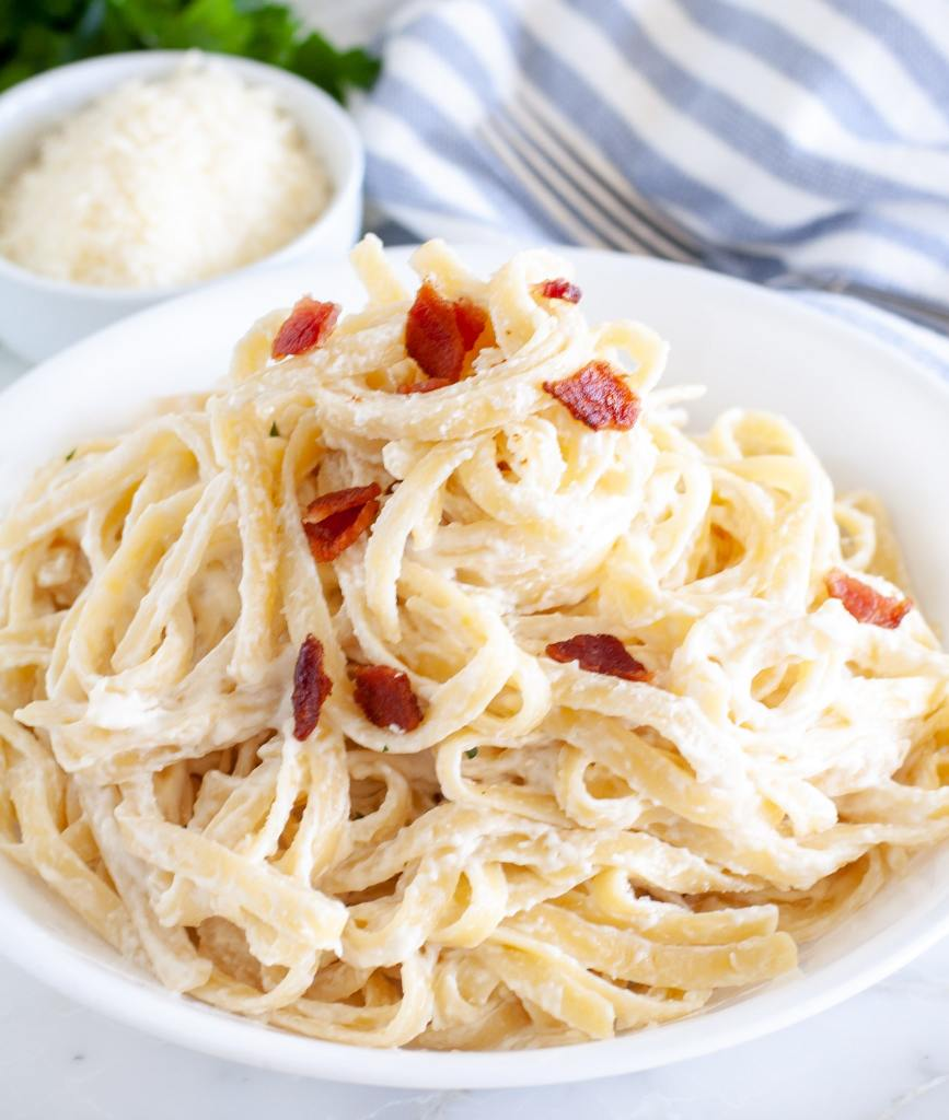Pasta on plate with cream cheese sauce and bacon bits
