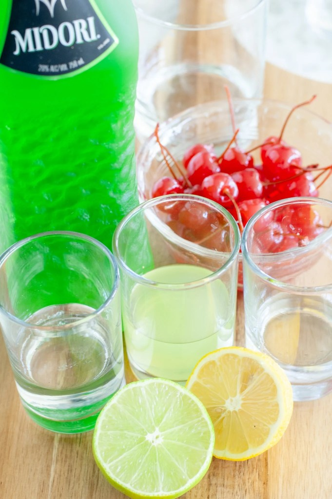 bottle of midori, bowl of cherries, lemon, lime and glass with vodka