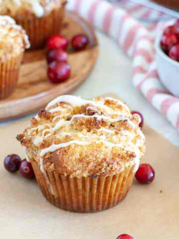 Muffins on a plate and on paper with cranberries.