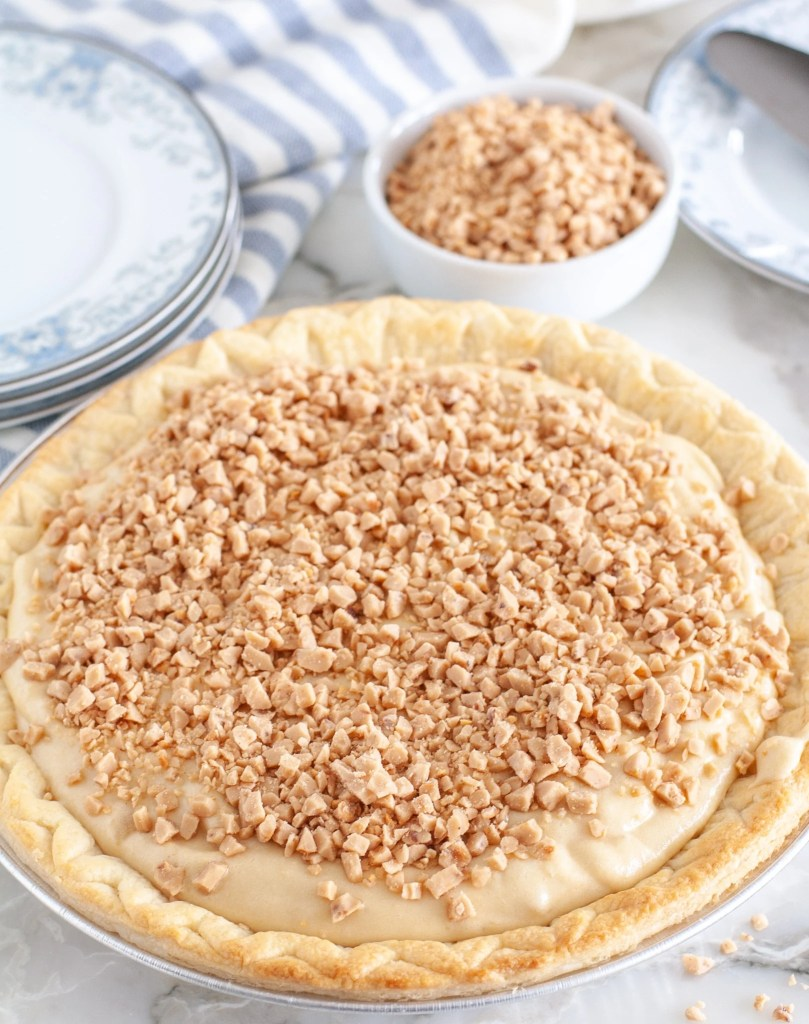 A whole pie topped with toffee bits.