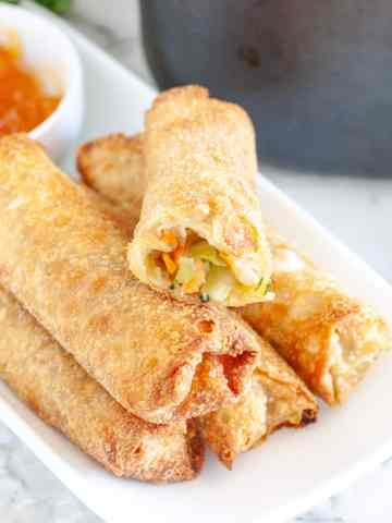 Plate of egg rolls with one that has bite taken out.