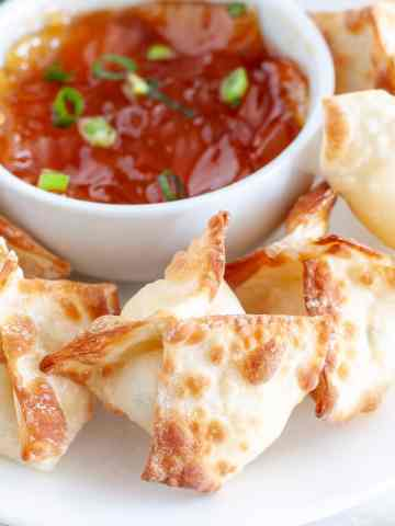 Wontons on plate with bowl of sauce.