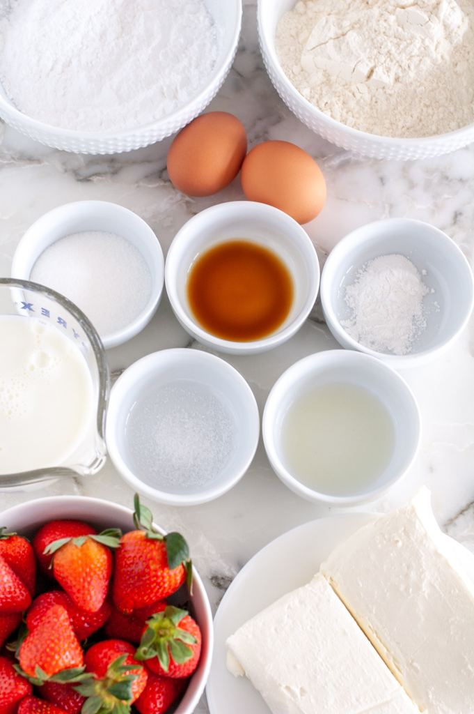 Bowl of strawberries, cream cheese, eggs, milk, sugar.