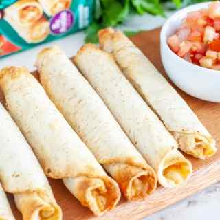 Cooked taquitos on a board with bowl of salsa.