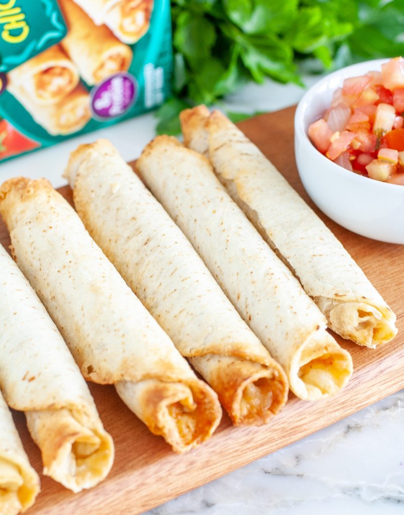 Taquitos on cutting board with bowl of salsa.
