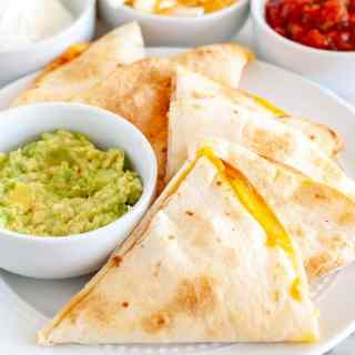 Quesadilla triangles on a plate with bowl of guacamole.