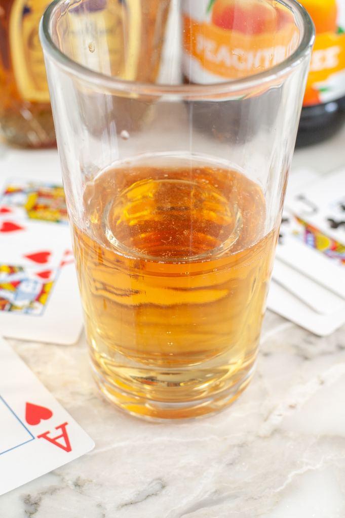 Camın yanında enerji içecekleri ve oyun kartları olan bir bardak.