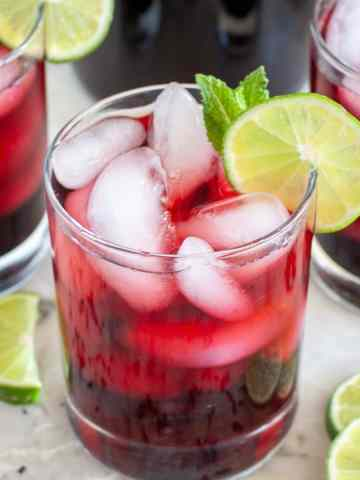 Glasses of hibiscus iced tea with lime slices.