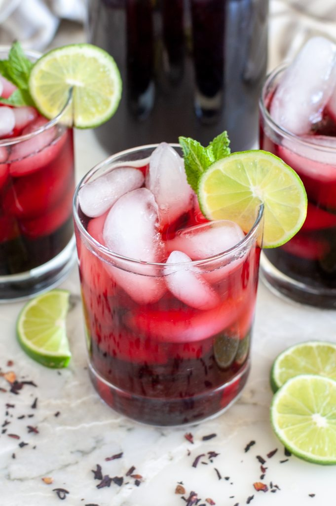 Glass of red tea with lime slice.