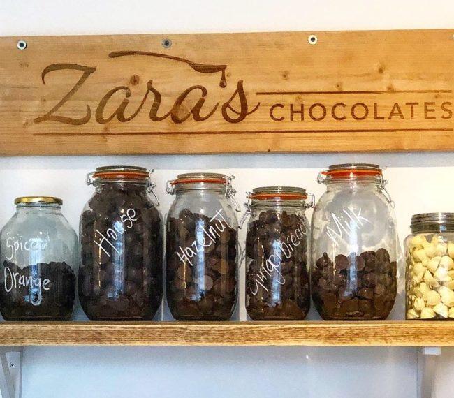 Zara's Chocolates Shelf of Hot Chocolate Jars and Shop Sign