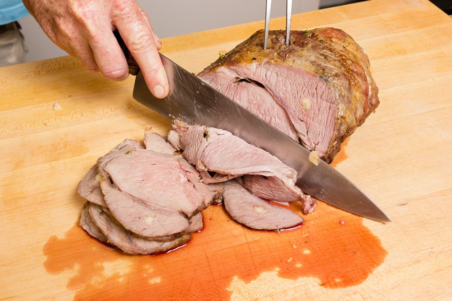 David Jackson slicing roast lamb stuffed with garlic during episode 01 of Food Over 50
