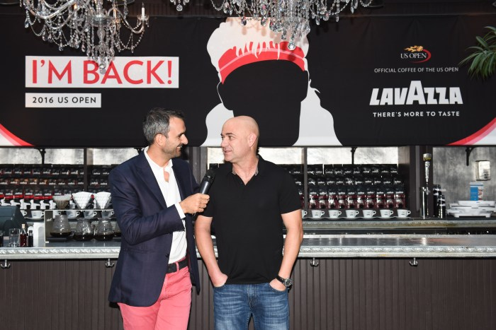 Andre Agassi (right) chats with coffee mogul Marco Lavazza (left) in front of a large silhouette of the ex-tennis star's former flamboyant hairstyle during the 2016 U.S. Open in NYC. (Photo: BFA/Leandro Justen)