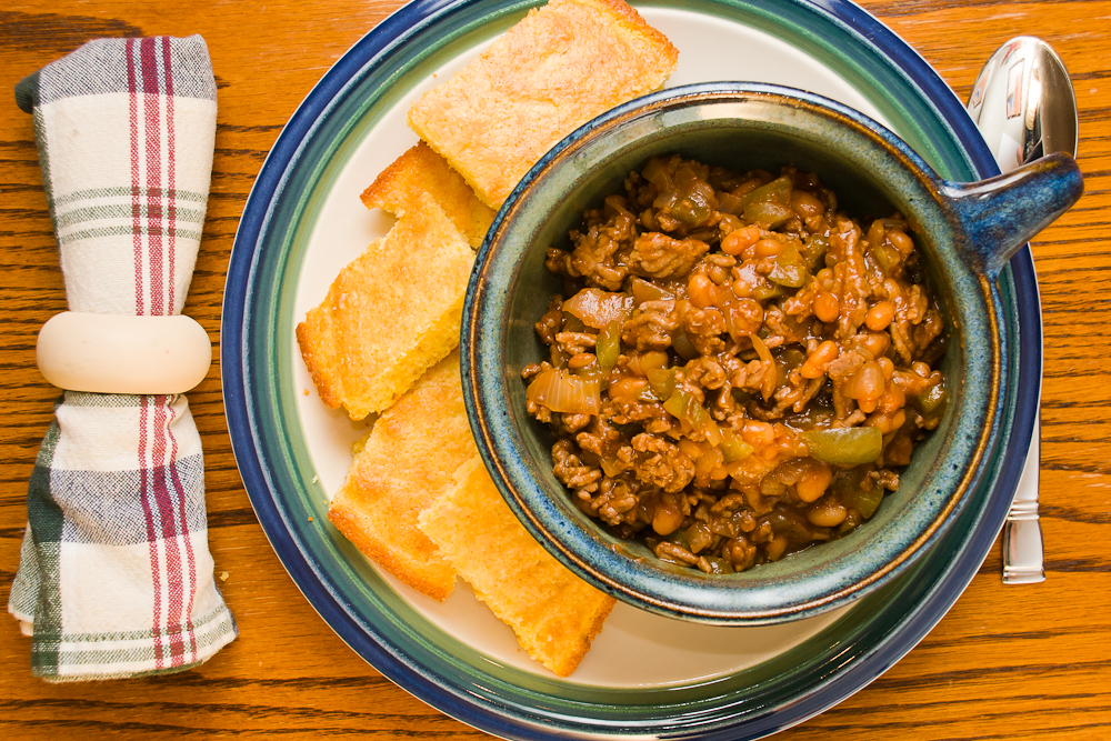 goulash in a bowl with a plate of cornbread