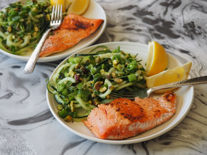 bright green cucumber noodles with pink wild salmon and yellow lemon wedges