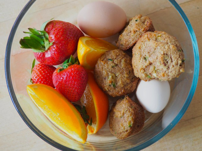 breakfast bowl of gluten free muffins hard boiled eggs strawberries and orange slices for healthy meal planning