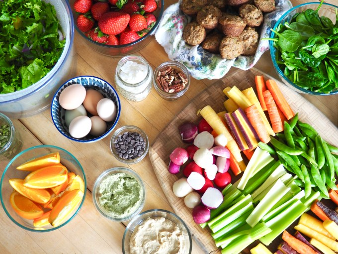 healthy meal prep table full of fruits vegetables eggs nuts muffins