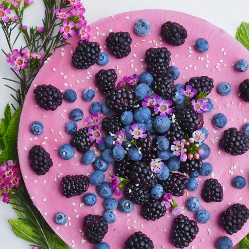 raw vegan blackberry lavender cheesecake from above with fresh flowers, blackberries, and blueberries