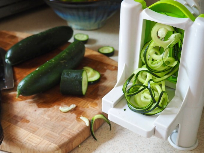 a cutting board with spiralizer making fresh cucumber noodles