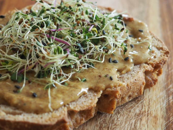 gluten-free toast with curried almond butter and alfafla sprouts