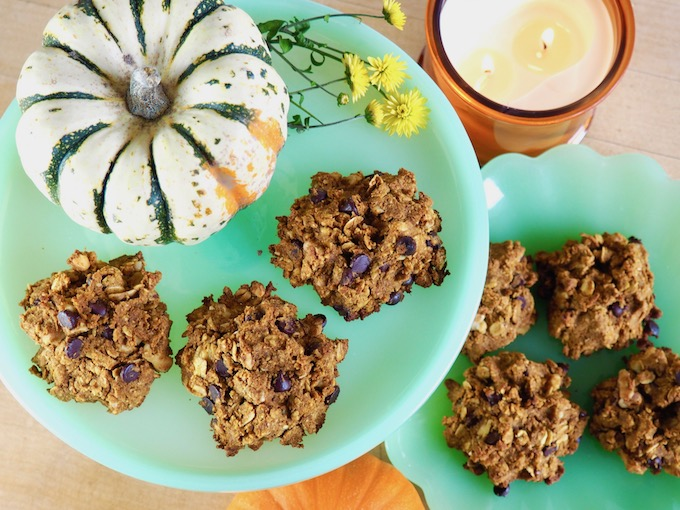 overhead view of Oatmeal Pumpkin Chocolate Chip cookies on green plates with a pumpkin and flowers