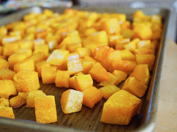 cubes of roasted butternut squash in a silver pan