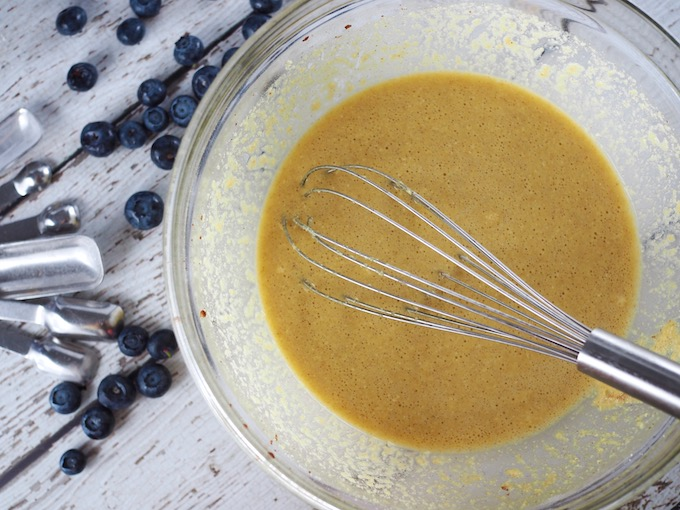 Coconut Flour Blueberry Skillet Bread batter in a glass bowl with whisk and teaspoons and blueberries