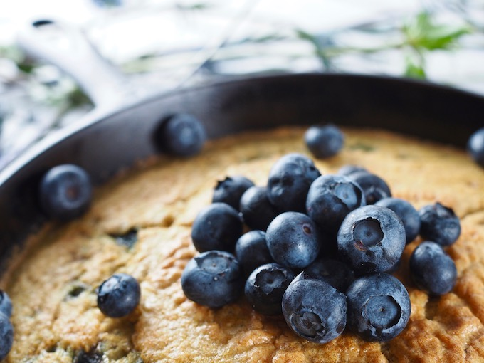 closeup of blueberries in cast iron skillet on Coconut Flour Blueberry Skillet Bread
